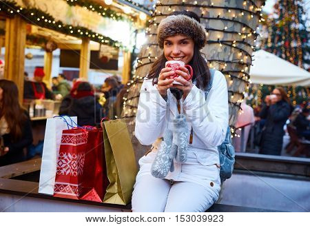 Young woman taking a rest during christmas shopping, smiling, drinking hot tea.