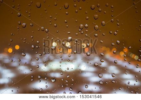 Raindrops on the Window With a Lightened City View