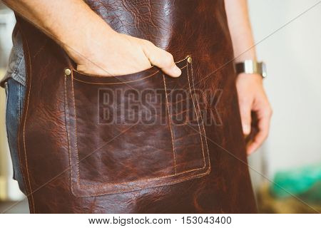 Close-up of unrecognizable coffee roaster holding hand in leather pocket of apron