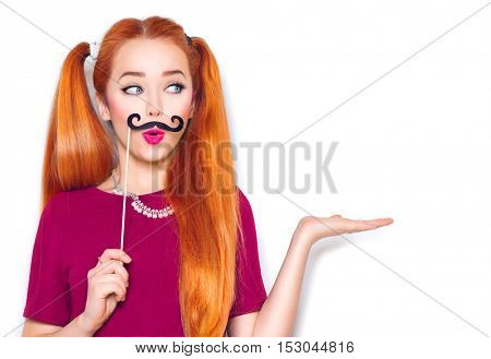 Beauty surprised funny teenage girl with paper mustache on stick showing empty copy space on the open hand palm for text, white background, presenting point. Proposing product. Advertisement gesture