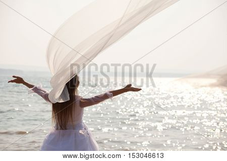 Bride standing near waterline with her arms raised