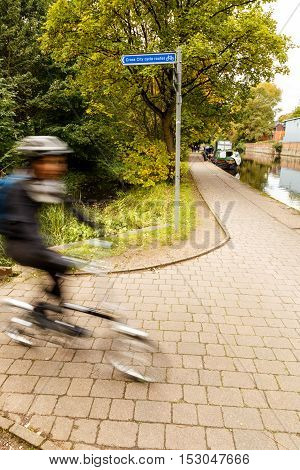 NOTTINGHAM ENGLAND - OCTOBER 19: Nottingham cross city cycle route signage and cyclist by the canal. In Nottingham England. On 19th October 2016.