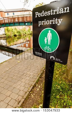 NOTTINGHAM ENGLAND - OCTOBER 19: Pedestrian priority sign installed by Canal & Rivers Trust alongside Nottingham canal. In Nottingham England. On 19th October 2016.