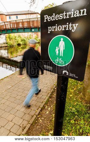 NOTTINGHAM ENGLAND - OCTOBER 19: Man walks past Pedestrian Priority sign alongside Nottingham canal. In Nottingham England. On 19th October 2016.