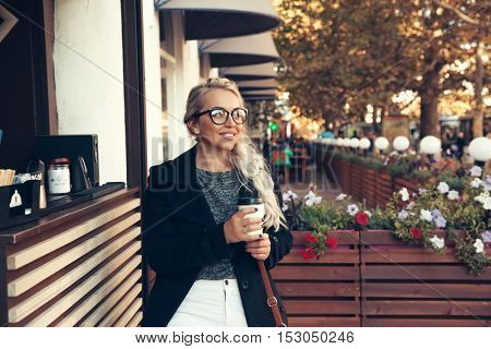 Blond woman wearing black midi coat, white pants, hipster glasses drinking take away coffee in paper cup in outdoor cafe on city street. Fall casual fashion, elegant everyday look. Plus size model.