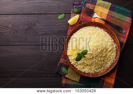 Couscous with mint and lemon in plate on dark rustic table from above. Copy space for text. Flat lay.