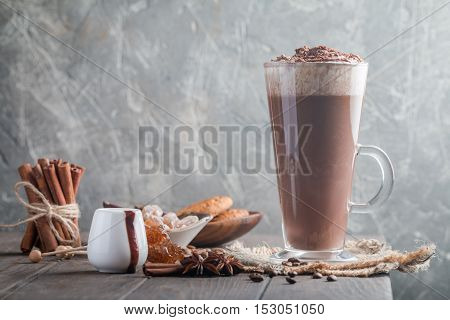 Coffee latte in a tall glass on the corner of wooden table