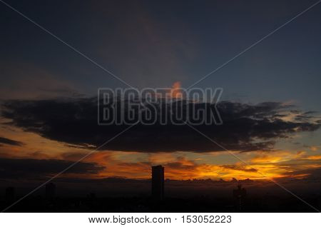 Independence Day Cloud hovers centrally over a solitary tall building rising from the darkness and silhouetted by the fiery sunrise behind.