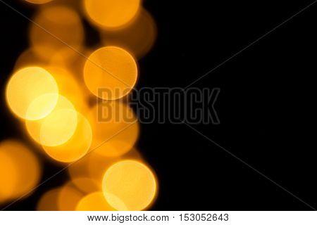 Bokeh orange circles on black background for Halloween. Festive christmas background.