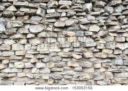 Gray pattern of old style design decorative cracked real stone wall surface with cement. Part of a stone wall, for background or texture. Antique natural stonewall background. Architectural background