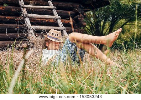 Summer in the countryside - little boy lies near the hayloft