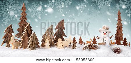 Wooden decoration arranged as a cute winter scene with a snowman conifer trees Christmas star animals and snow on a snowflakes background