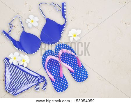 Fashionable woman swimming suit and flip flop on sand beach background