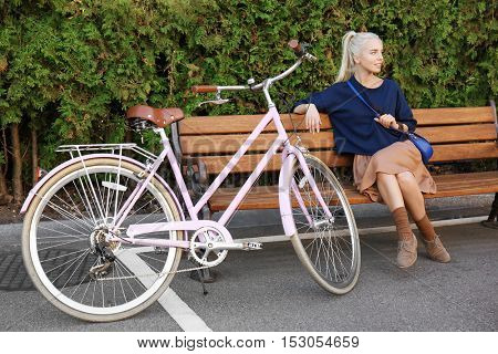 Pretty young bicyclist sitting on bench in park