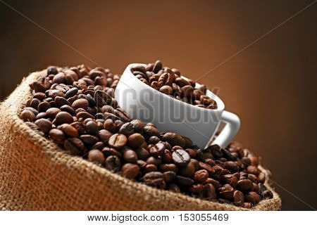 Sack with roasted coffee beans and white cup on dark background, close up view