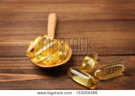 Cod liver oil capsules in spoon on wooden background