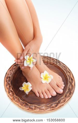 Beautiful womens legs and frangipani flowers over white blue background, beauty treatment, perfect skin waxing, pedicure in spa salon