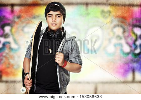 Active teenager with a skateboard, colorful urban graffiti wall background, enjoying outdoors sport, stylish hipster look