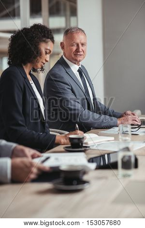 Portrait of a smiling mature businessman sitting at a boardroom table with a diverse group of colleagues