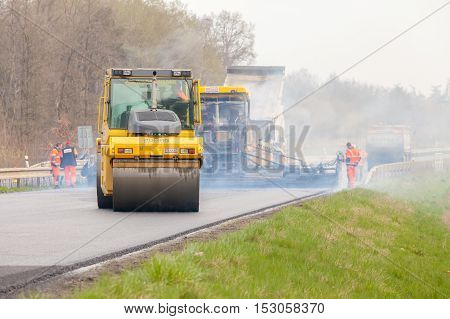 CZECH REPUBLIC, PLZEN, 10 APRIL, 2016:Asphalt spreading machine and vibration roller  at pavement road works.