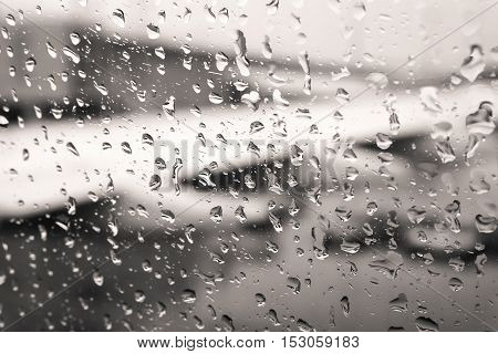 Defocused view of airplane wing through passenger window with rain drops. Processed with vintage style