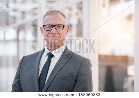 Portrait of a confident mature businessman in glasses standing in the lobby of a modern office building