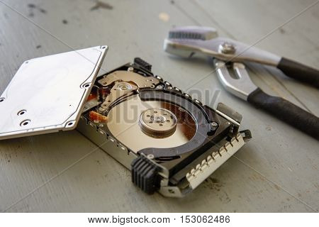 Broken And Destroyed Hard Drive Disk On Wooden Table