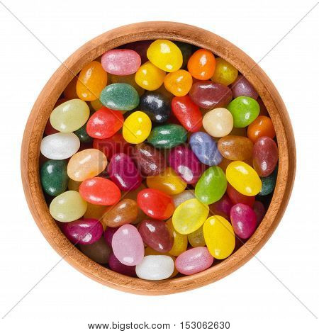 Jelly beans in wooden bowl on white background. Assorted small bean-shaped sugar candies in different colors with soft candy shells and gel interiors. Isolated macro food photo close up from above.
