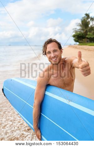 Surfer guy happy with surf surfing smiling doing thumbs up hand sign at camera after fun surf session in ocean waves on beach vacation. Surfing travel destination. Handsome sexy man topless.