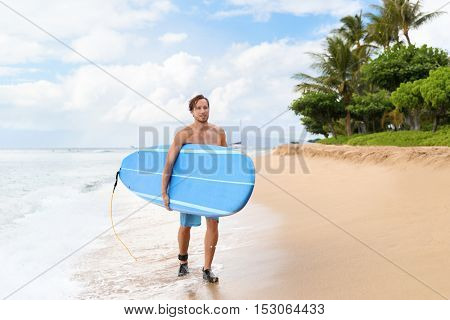 Surfer man surfing on maui beach hawaii, usa. Handsome male athlete walking carrying blue long surfboard going for a surf session on kaanapali beach, hawaiian destination.