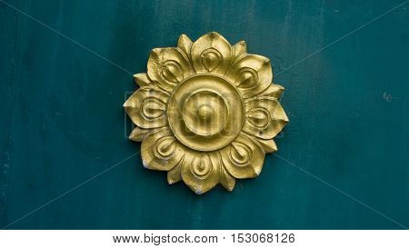 Lotus logo of flower Thai style classic sculpture on the green wall background.