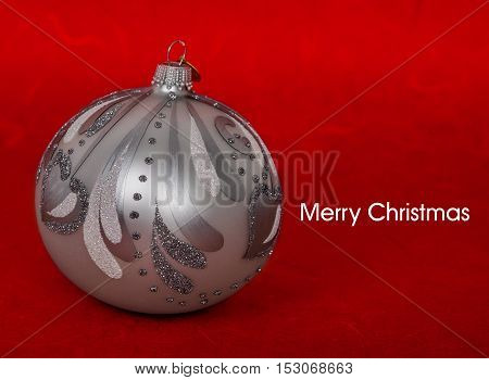 Silver Christmas bauble on red abstract background