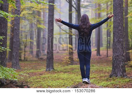 Woman worshiping with open arms in an autumn misty forest with yellow green and red leaves