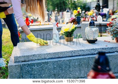 Woman Cleans A Grave With Sponge.