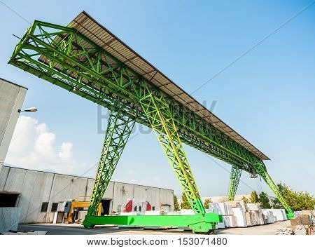Green gantry crane at work in a warehouse of marble blocks