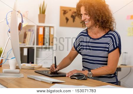 Middle age designer working on a desktop with a stylus pen