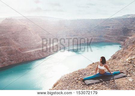 Young sporty girl wearing blue activewear stretching outdoors. Woman training yoga pose on mountain hill, calm and silent view.