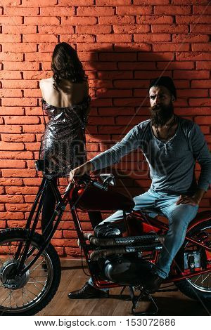 pretty sexy cute woman or girl near young handsome bearded man hipster or biker with long beard sitting on metallized motorbike or motor cycle with wheels on red brick wall background in garage