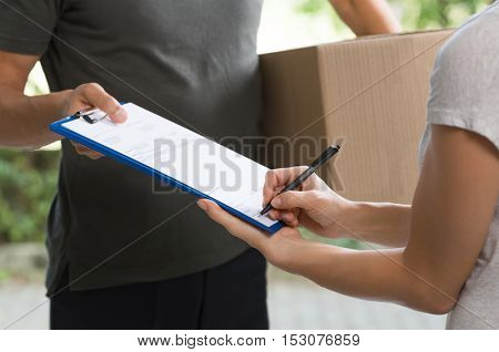 Woman signing receipt of delivery package. Courier man carrying large parcel while woman confirming delivery. Close up of woman han signing while receiving courier from delivery man.