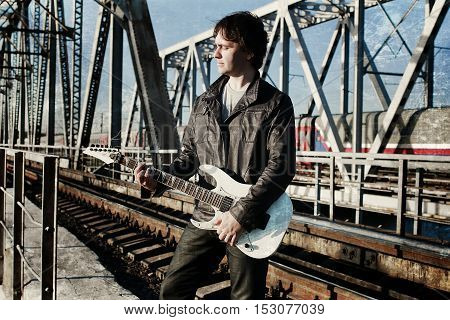 a young man in a leather biker jacket with electric guitar on the street in spring day