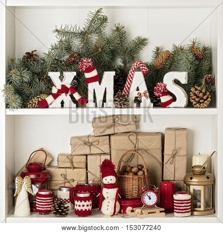 Merry Christmas! Wooden letters XMAS in knitted hats and scarf in red and white color on the background of fir branches with cones. Gifts toys and candles. Christmas card.