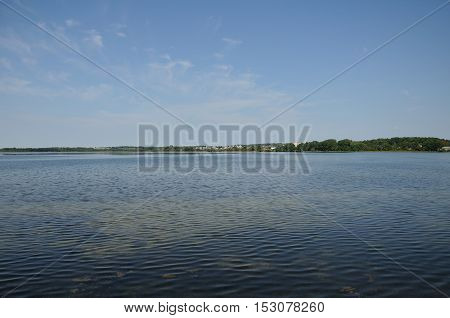 horizontal green coastline of the summer lake under the blue sky