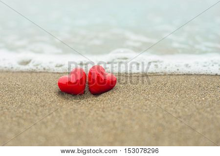 Two red hearts on a background of beach and sea. Valentines Day concept