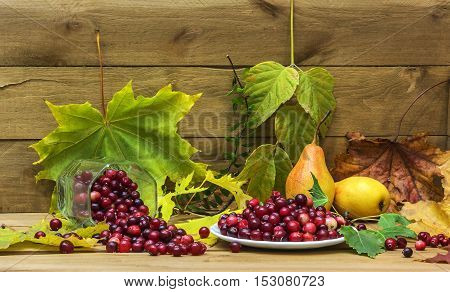 Against the background of a wooden surface surrounded by yellow autumn leaves lie pears and cranberries in a glass and fallen white saucer