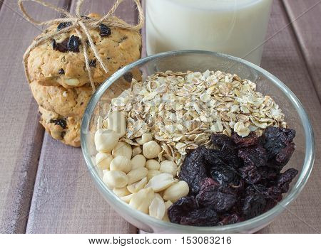 Ingredients for baking healthy cookies in glass bowl with pile of ready cookies and glass of milk