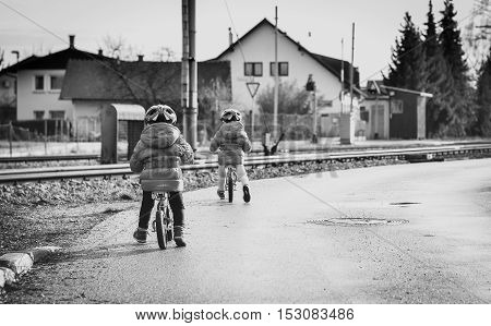 Twins children riding balance bikes on the road with helmet. Young toddlers with in bicycle helmet are riding bikes in the winter on the road with railroad tracks near by