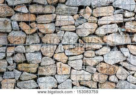 Wire Gabion Rock Fence. Metal Cage filled with rocks. Texture background of rock fence with cage.