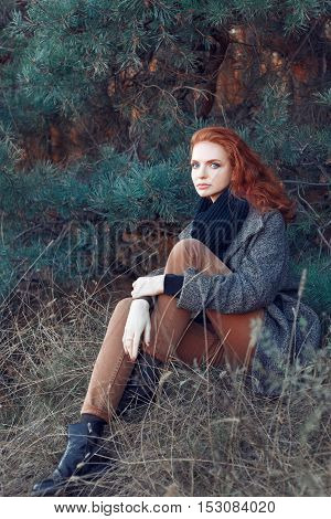 Beautiful elegant red-haired woman sitting in park in autumn. Redhead girl in autumn clothes in the forest. Redhead woman outdoor in autumn park weared scarf and coat looking at camera