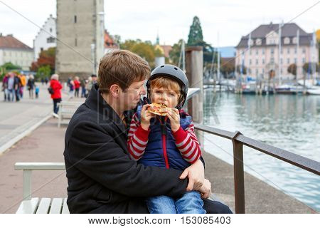 Happy dad holding his son, little funny kid boy on arm, on cold day, walking together in a city. Father hugging, son eating pizza. Happy, joyful family.