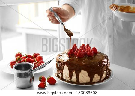 Female chef making caramel cake with strawberries